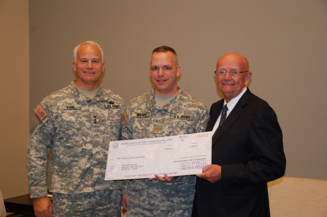 "Then-Maj. Greg Motes, winner of the ""Capabilities for Army Future Force"" writing contest hosted by the U.S. Army Capabilities Integration Center and the Assocation of the United States Army receives the $1,000 prize from Lt. Gen. Michael Vane, ARCIC director, and retired Gen. Gordon Sullivan, president of AUSA, during the AUSA National Meeting here in Washington, D.C."