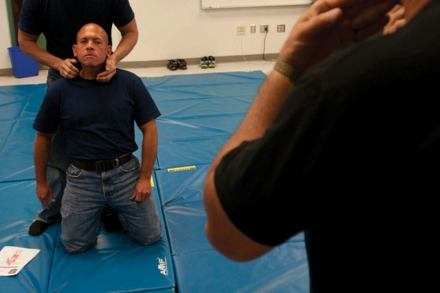Police Officer and Department of the Army Security Guard training course instructor Richard Olmeda shows recruits how to properly execute pressure point strikes at Fort Buchanan Jan. 27.