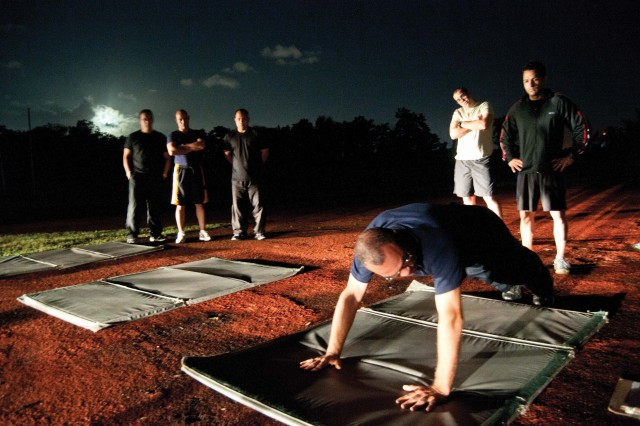 Police Training Officer, Lt. Felipe Deida demonstrates a properly executed pushup to recruits at Fort Buchanan's Track in the early morning hours of Jan. 19. The recruits began their Department of the Army Security Guard this day and graduated from the course Feb. 9.