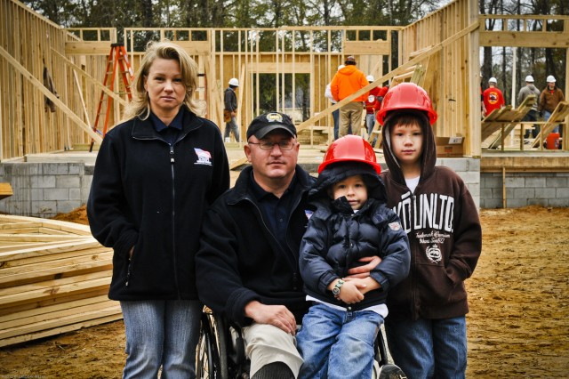 Standing in front of the foundation of their new house from the organization Homes for our Troops, the Letterman family (from left to right) Elena, retired Staff Sgt. Letterman, Alex (age 5), and Daniel (age 12) prepare for the big move into their new home as volunteers within the community of Hinesville as well as Soldiers from 2nd Heavy Brigade Combat Team, 3rd Infantry Division come out to lend a hand, Jan. 21.