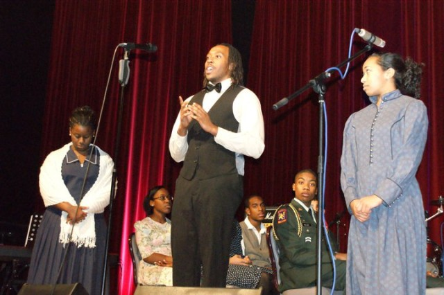 "Jasmine Coney, left, stands next to Dominique Tolbert, Da'Von  Loney and Jeremiah Miller who pose as riders on the Freedom Train as Devon Meachum, center, portrays Frederick Douglass and Camille Jackson, right, portrays Harriet Tubman in ""Harriet Tubman's Journey to Freedom"" performed by the Junior Association for the Advancement of Minorities."
