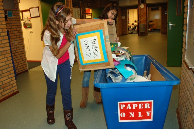 AFNORTH International School sixth-graders, Riley Daniels (L) and Jade Huberty (R) dump paper into one of the additional recycle bins that the school put into service after a recommendation arose from last year's Tri-Border AFAP Conference.