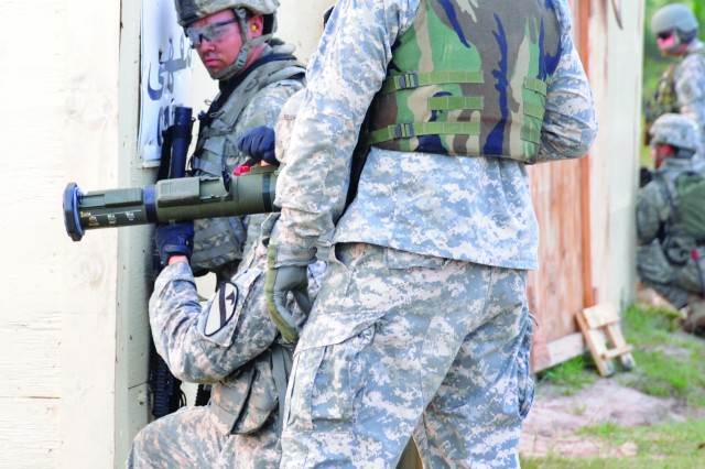 A 1st Cavalry Division Soldier prepares to fire an anti-tank weapon while a range operations trainer-mentor looks on during the group's live-fire exercise at the Joint Readiness Training Center, Fort Polk, La., in June.