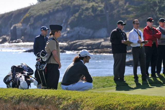 PEBBLE BEACH, Calif. - Seaman Christina Larson stands behind Kenny G on the 18th green of the Pebble Beach Golf Course during the 3M Celebrity Challenge. Larson was one of a handful of foreign language students from the nearby Defense Language Institute Foreign Language Center in Monterey who acted as caddie for the musician. Active-duty service members were admitted free on Feb. 9 as part of Military Day at the weeklong AT&T Pebble Beach Pro-Am golf tournament.