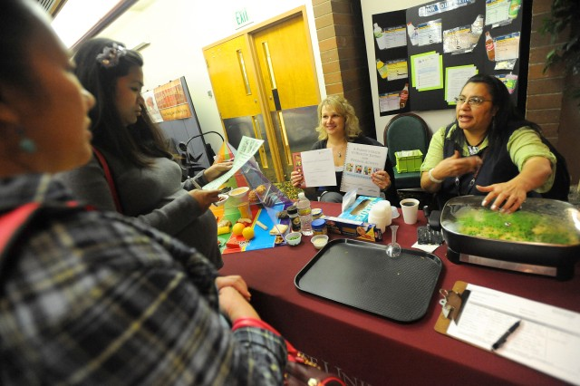 Svetlana Melnichuk, center, and Lynette Frye talk about the Washington State University nutrition education program with Joy Rabot, left, and Cindy Parrett during the third annual Operation Care Fair Feb. 5 at McChord Field.
