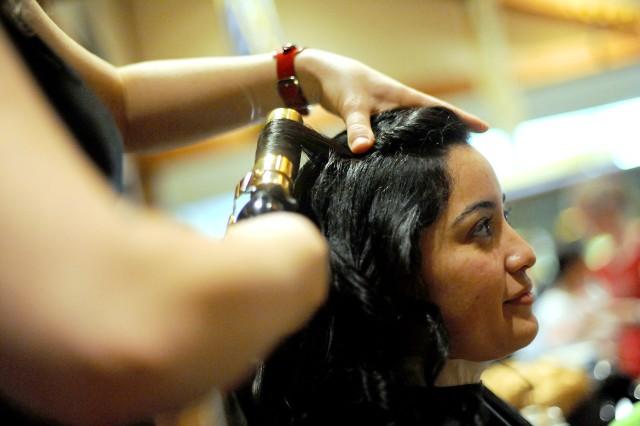 Vera Willis, a McChord Field employee, relaxes as stylist Alycia Hodapp curls her hair.