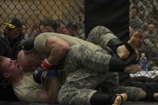 First Lt. Daniel Suden, 94th Engineer Battalion, blue glove, fends off an attack by Fort Riley fighter, Air Force Staff Sgt. Steven Tamburo, 10th Air Support Operations, red glove, during the first post-versus-post combatives tournament, Friday, at Davidson Fitness Center on Fort Leonard Wood, Mo. Fighters from Fort Riley, Kan. and Fort Leonard Wood competed in seven weight classes. Fort Riley won four of the seven matches for the bragging rights.