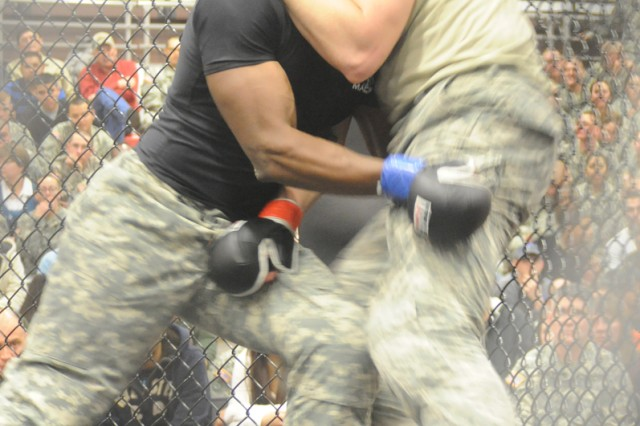 Sgt. 1st Class Jermaine Bruce, Company A, 3rd Battalion, 10th Infantry Regiment, pushes Pfc. Hans Haken, Fort Riley, against the cage during the light heavyweight match in Davidson Fitness Center on Fort Leonard Wood, Mo., Feb. 4. The match was part of the first inter-post competition in combatives between Fort Riley, Kan. and Fort Leonard Wood.