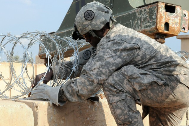 BABIL, Iraq - A 3rd Armored Cavalry Regiment Soldier ties a strand of razor wire to a barrier on Contingency Operating Site Kalsu Friday. The wire is being used as a force protection measure for the Iraqi Army compound that will soon be opened on Kalsu. The compound will allow for an increase in training and mission opportunities for Iraqi and American forces in Babil. (110211-A-8856R-026)