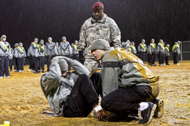 Sgt. 1st Class Eric Lloyd, a paratrooper with 1st Battalion, 504th Parachute Infantry Regiment, 1st Brigade Combat Team, 82nd Airborne Division, grades the sit-up event of an Army Physical Fitness Test, or APFT, during early-morning rain Jan. 19, 2011, at Fort Bragg, N.C.