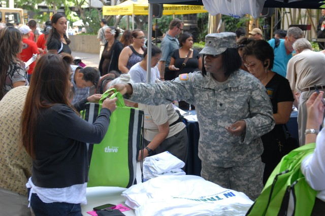 Spc. Tameika Drayton, an  8th Theater Sustainment Command volunteer, hands out special giveaways to people who showed up for the Great Aloha Run early registration at the Kaiser Permanente Great Aloha Run Kick Off Party, Dec. 2, 2010.