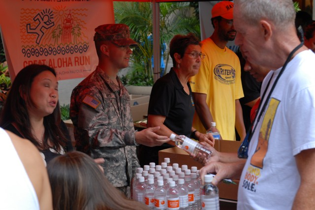 Pfc. Joseph Peck, an 8th Theater Sustainment Command volunteer, hands out water to participants signing up for the Great Aloha Run at the Kaiser Permanente Great Aloha Run Kick Off Party, Dec. 2, 2010.