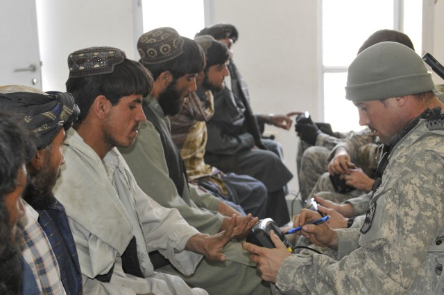 WEESH, Afghanistan - U.S. Army Sgt. Payton Westerfield, assigned to Blackjack Troop, 1st Squadron 38th Cavalry Regiment, 525th Battlefield Surveillance Brigade, based in Fort Bragg, N.C., a native of Ridgeland, S.C., processes an Afghan man using the Handheld Interagency Identity Detection Equipment at the customs office in Weesh Feb. 4. (U.S. Army photo by Sgt. Richard Andrade / 16th Mobile Public Affairs Detachment)
