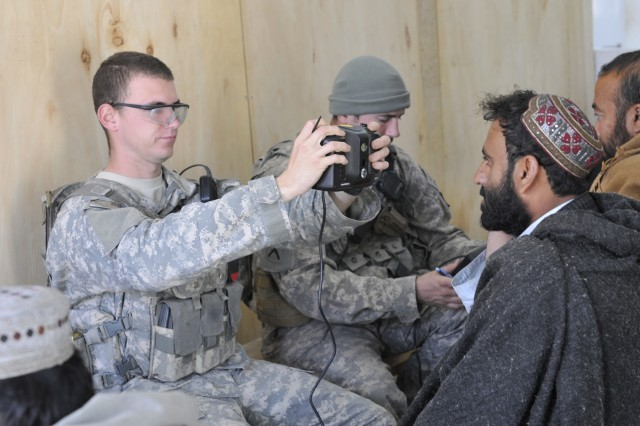 WEESH, Afghanistan - U.S. Army Sgt. James Stewart assigned to Blackjack Troop, 1st Squadron 38th Cavalry Regiment, 525th Battlefield Surveillance Brigade based in Fort Bragg, N.C., a native of Kokomo, Ind. processes an Afghan man using the Handheld Interagency Identity Detection Equipment at the customs office in Weesh Feb. 4. (U.S. Army photo by Sgt. Richard Andrade / 16th Mobile Public Affairs Detachment)