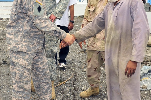 Lt. Col. Jeffrey Jurasek, 402nd Civil Affairs Battalion commander (left) shakes hands with Farid Ali, headmaster of the Chomoni Primary School for Children, in Chomoni, Comoros, Jan. 24, 2011.