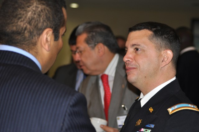 Lt. Col. Uli Calvo, North Africa Desk Officer, Security Cooperation Directorate, U.S. Army Africa, speaks with a delegate at the Marrakech Security Forum in Marrakech, Morocco, Jan. 20. Belgian Defense Minister Pieter De Crem is at rear.