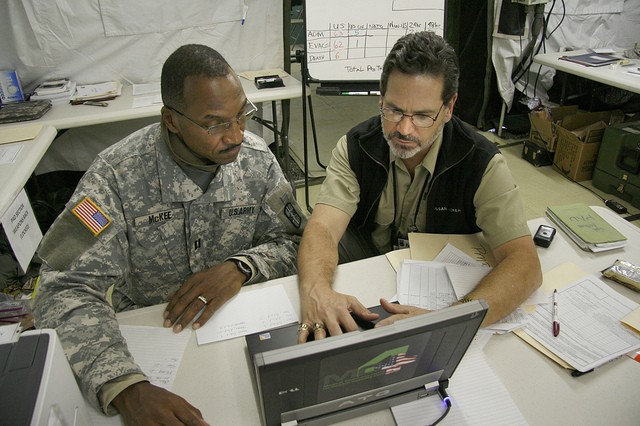 Dr. Greg Jolissaint, medical director and chief for MC4's Clinical Operations Office, teaches Capt. Harry McKee Sr., patient administration officer with the 256th Combat Support Hospital, to use the MC4 system during a pre-deployment training exercise at Joint Base Lewis-McChord, Wash.