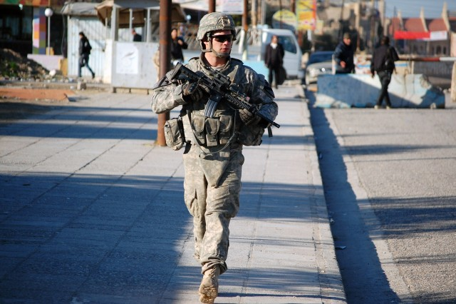Spc. Joshua Jacobsen, an infantryman assigned to Company B, 2nd Battalion, 7th Cavalry Regiment, 4th Advise and Assist Brigade, 1st Cavalry Division, walks through the city of Qara Qosh, Iraq, pulling security during a joint patrol Feb. 9, 2011.
