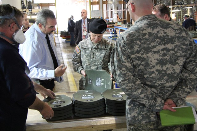 Mr. John Dingman, second left, explains to Gen. Ann E. Dunwoody, AMC CG, the repair process SIAD conducts on Enhanced Small Arms Protective Insert (ESAPI) plates that have exhibited some form of External Material Failure.