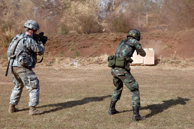 U.S. Army Alaska and Thai forces fire each others' weapon systems at Camp Erawan, Thailand. The U.S. Soldier fires the Thai TAVOR-21 rifle, while the Thai soldier fires the U.S. M-4 carbine rifle.