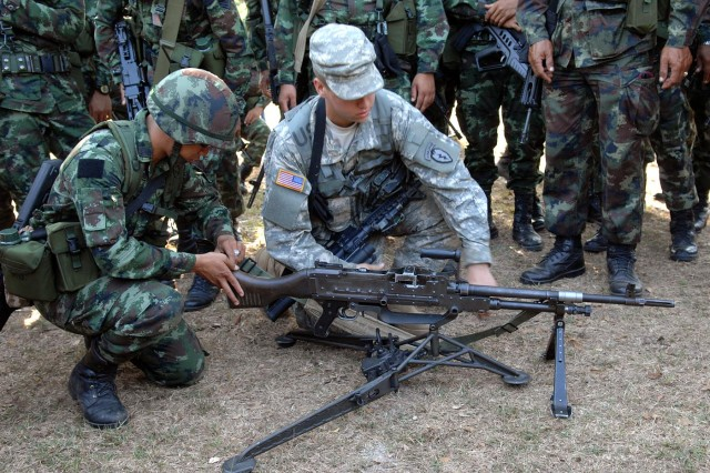 A paratrooper from the Alaska-based 3rd Battalion, 509th Parachute Infantry Regiment and his Royal Thai Army counterparts go over drills on the M-204 Bravo machine gun Feb. 10 at Camp Erawan, Thailand, during Cobra Gold 2011. Both armies use the M-204.