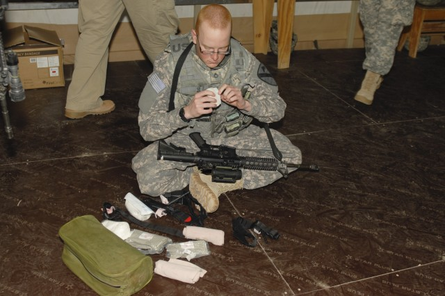 CAMP BUEHRING, Kuwait - Pfc. Adam Miller, with the Personal Security Detachment, Headquarters and Headquarters Troop, 3rd Advise and Assist Brigade, 1st Cavalry Division, prepares his first aid supplies during a medical-simulation training event, Feb. 12.