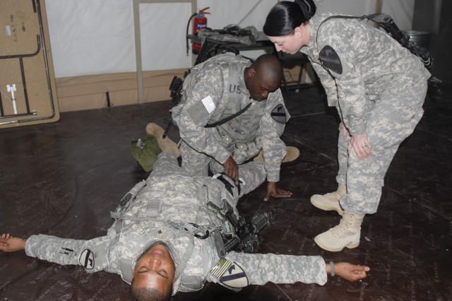CAMP BUEHRING, Kuwait - Pfc. Mary Covington (right) checks Spc. Everette Withers' work as he applies a tourniquet to Spc. Bryen Reid's leg during a medical-simulation training event Feb. 12.