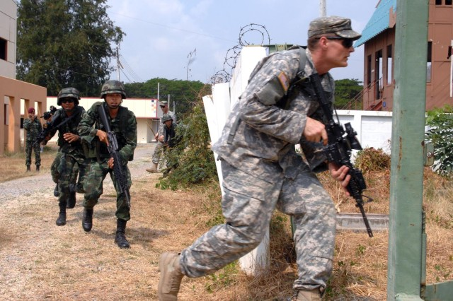 U.S. and Thai paratroopers rush into a training building at the Camp Erawan MOUT Site in Thailand Feb. 12 during Cobra Gold 2011.