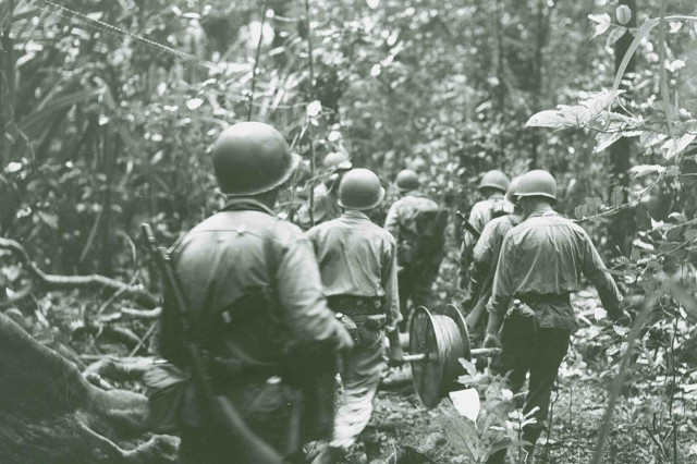 American Soldiers run communications wire through thick jungle on New Georgia for the 172nd Infantry Regiment, 43rd Signal Company, 43rd Infantry Division on July 6, 1943.