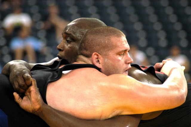 Staff Sgt. Dremiel Byers (right), a member of the U.S. Army World Class Athlete Program at Fort Carson, Colo., and 2000 Olympic gold medalist Rulon Gardner clinch during a battle of world champions in the 2004 U.S. Olympic Wrestling Team Trials at the RCA Dome in Indianapolis. Gardner won the 264.5-pound Greco-Roman division with a pair of 2-1 overtime victories over Byers to earn a berth in the Olympic Games at Athens, Greece.