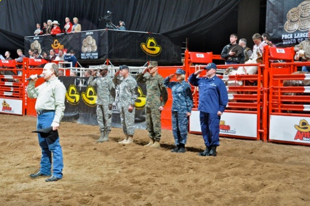 Rodeo announcer Hadley Barrett sings the national anthem as military representatives Gen. Edward Rice, Maj. Gen. Perry Wiggins, Maj. Jeremiah Salame, Capt. Tina Ortiz and Lt. Cameron McCampbell salute the colors.