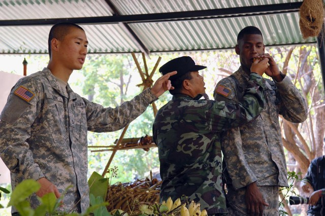 Pfc. Ativut Son interprets the instructions of a Thai jungle expert on edible plants during a survival class for the U.S. paratroopers at the Special Warfare School at Camp Erawan, Thailand. Son is a utilities equipment repairer with the 71st Chemical Company, 8th Military Police Brigade, based at Schofield Barracks, Hawaii, and attached to the 3rd Battalion, 509th Parachute Infantry Regiment for Cobra Gold 2011.
