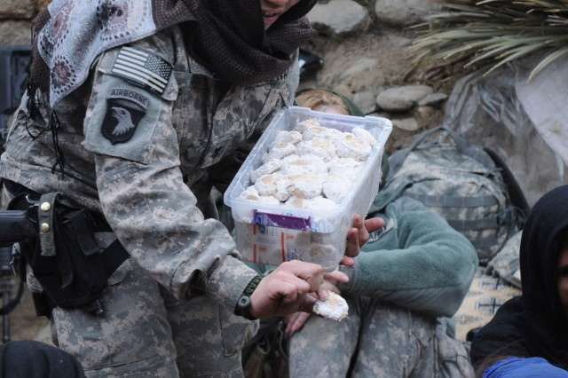 U.S. Navy Culinary Spc. 2nd Class Francine Henry, with the Khowst Provincial Team, gives cookies she baked to local Afghan women at a women's shura held in Jaji Maidan in Khowst Province, Afghanistan, Thursday, Feb. 10. She had attended the first women's shura held in the area with coalition forces and was part of an all-female mission to interact at the shura. One of the issues the women raised during the shura was the need for medical care for themselves and their families. (Photo by U.S. Army Spc. Tobey White, Task Force Duke Public Affairs Office)