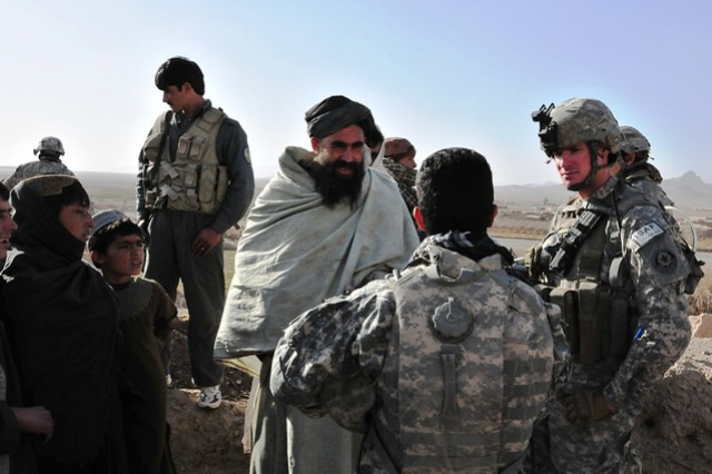 First Lt. Andrew Murphree, Platoon Leader for 2nd Platoon, Outlaw Troop 2nd Stryker Cavalry Regiment, and his interpreter talk with a village elder near the town of Sha Wali Kot. Meeting with the locals in key leader engagements keeps the locals, as well as coalition forces, informed about activities in the area.