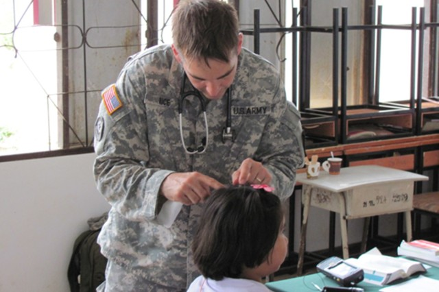 Lt. Col. Matthew S. Rice, from the 65th Medical Brigade, examines a Thai patient as part of Eighth Army's participation in Operation Cobra Gold.