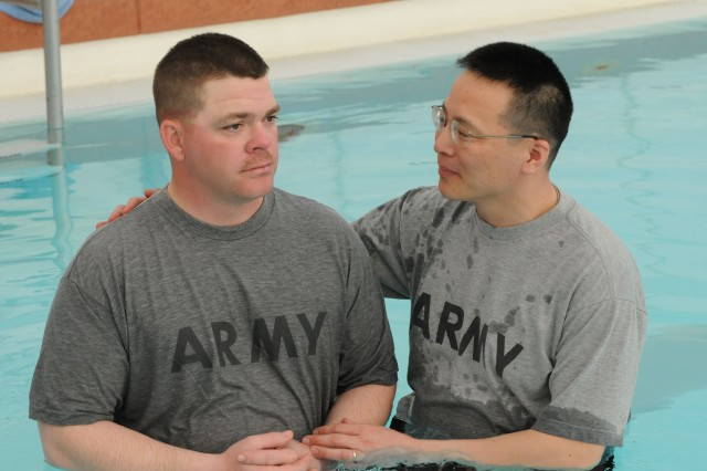 U.S. Army Sgt. John Gladden, a supply specialist currently serving with the 25th Brigade Support Battalion, 1st Stryker Brigade Combat Team, 25th Infantry Division, Fort Wainwright, Alaska, waits with Capt. Jungu Lee,the 25th BSB chaplain, to be baptized at the U.S. Army's National Training Center in Fort Irwin, Calif. Feb. 9. Gladden and Lee are both currently deployed with the 1-25th to NTC and are completing an intense rotation in preparation for the Brigade's upcoming deployment to Afghanistan.