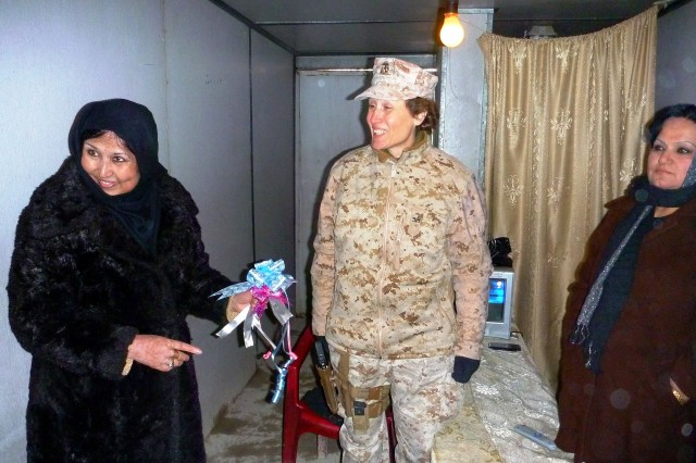 Col. Sheila Scanlon and Shafiqa, a first lieutenant in the Afghan National Police (left),  share a light moment in the old female security-search conex after the ceremony.