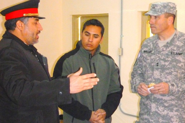 Maj. Gen. James B. Mallory, deputy commanding general, NATO Training Mission-Afghanistan/ Combined Security Transition Command - Afghanistan and Brig. Gen. Joma Adeel, commander, Kabul International Airport, Afghan National Police, engage in conversation after the ceremony in a different building set up with refreshments.