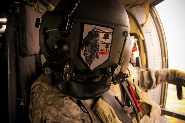 Keeping one hand on his weapon, Black Hawk crew chief Spc. Christopher Wilmeth turns in his seat to inspect the cabin Feb. 10, during a mission near Baghdad.