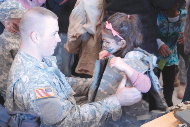 With a little help from Pfc. Derek Mc Creary, Amaya Dickey, 5, tries on body armor Feb. 12, during Youth Mock Deployment IV. Children attending the one-day deployment exercise were able to try on Kevlar helmets, vests and other gear typically worn by their parents on deployment.