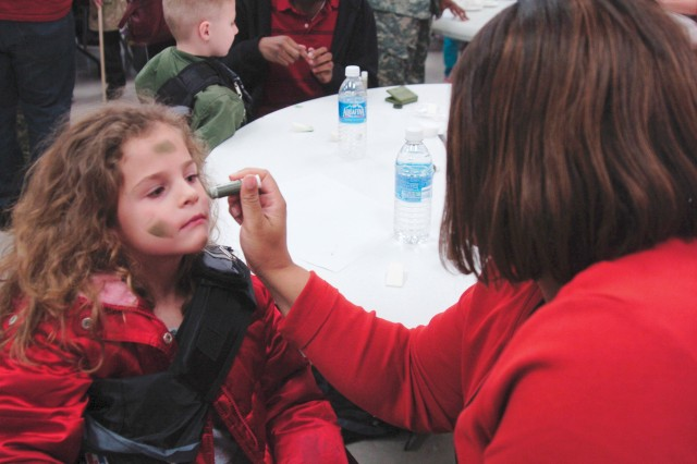 Hope Cowden, 5, gets her face painted by volunteer Kaili Stanton Feb. 12, at Comanche Chapel at Fort Hood, Texas, during Youth Mock Deployment.