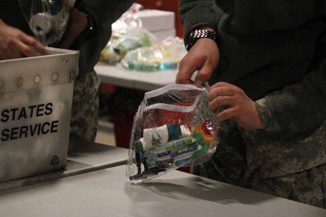 FORT HOOD, Texas-A Soldier with the Task Force Lobos, 1st Air Cavalry Brigade, 1st Cavalry Division, zips up a finished care package for a deployed troops at the Soldiers' Angels headquarters in San Antonio, Feb. 10.