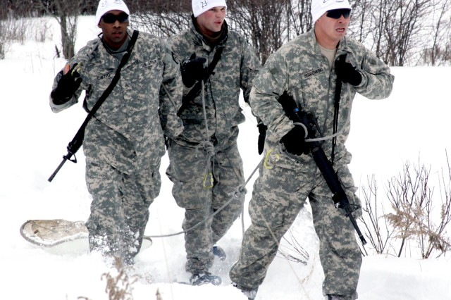 Team Raptors, composed of 2nd Lt. Patrick Zebrowski, Sgt. Lawrence Ewing and Spc. Adam Boylan, 10th Sustainment Brigade Troops Battalion, 10th Mountain Division (LI), fight their way through the snow pulling an Ahkio sled during Muleskinner Challenge III at Fort Drum.