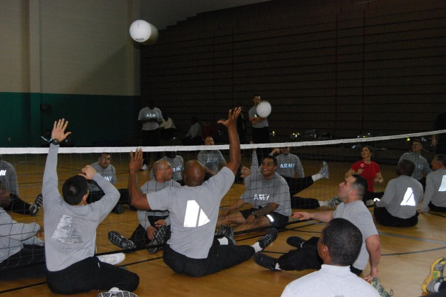 Soldiers from the Warrior Transition Battalion participate in seated volleyball during the U.S. Paralympic Expo at Newman Fitness Center, Feb. 10. The players sit on the floor on the volleyball court, participating in a low-impact adaptive sport method.