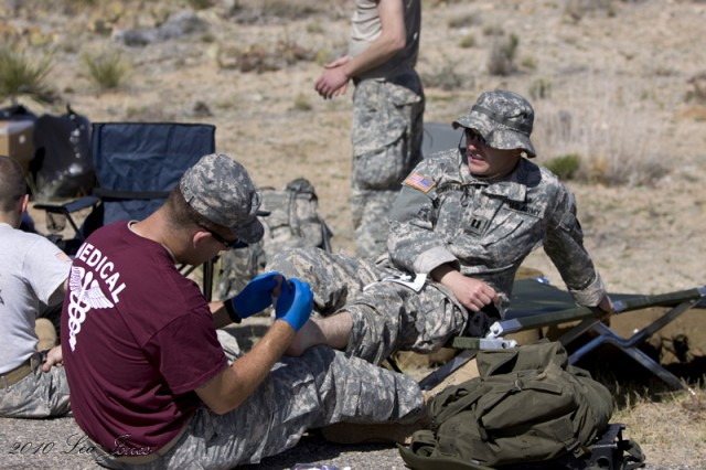 A volunteer medic applies a dressing to a participant's blisters.