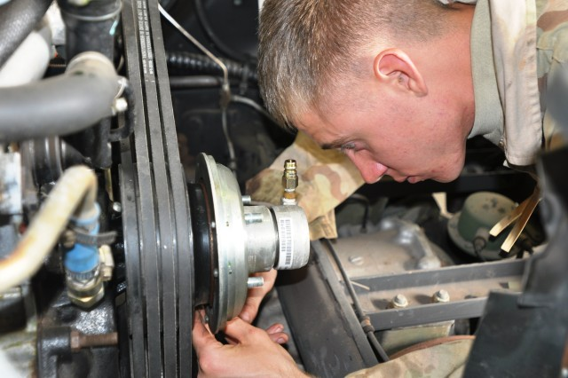 """Specialist Joshua Michael, a wheeled vehicle mechanic, assigned to Headquarters and Support Company, 209th Aviation Support Battalion, """"Lobos,"""" 25th Combat Aviation Brigade, loosens a bolt for removal of the fan clutch on a High Mobility Multi-Purpose Wheeled Vehicle at the motor pool at the Pohakuloa Training Area, on the Big Island of Hawaii, Feb. 7.  (Photo by: Sgt. Daniel Schroeder  25th Combat Aviation Brigade Public Affairs)"""