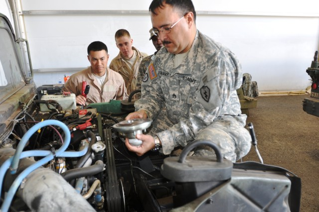 """Staff Sgt. Mario Fernandez, Motor Sergeant, Headquarters and Support Company, 209th Aviation Support Battalion, """"Lobos,"""" 25th Combat Aviation Brigade, gives a quick lesson on the fan clutch for a High Mobility Multi-Purpose Wheeled Vehicle to two of his Soldiers at the motor pool during a rotation to the Pohakuloa Training Area, on the Big Island of Hawaii, Feb. 7.  (Photo by: Sgt. Daniel Schroeder  25th Combat Aviation Brigade Public Affairs)"""