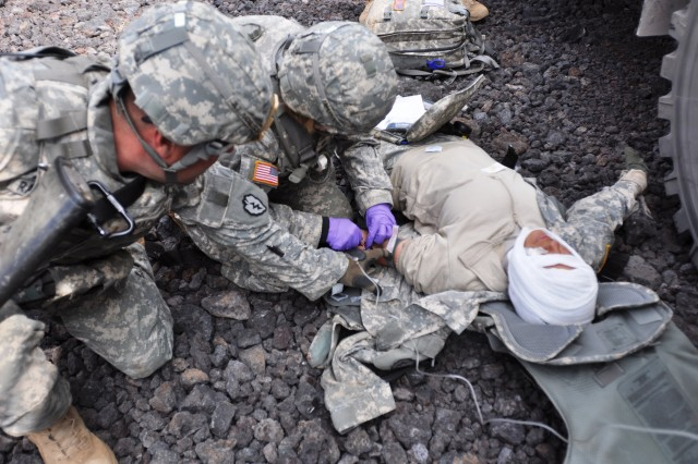 """Soldiers assigned to A Company, """"Alpha Dawgs,"""" 209th Aviation Support Battalion, 25th Combat Aviation Brigade, administers an intravenous solution to a wounded Soldier while conducting a convoy live fire situational training exercise during the Pohakuloa Training Area, on the Big Island of Hawaii, Feb. 11.  (Photo by: Sgt. Daniel Schroeder  25th Combat Aviation Brigade Public Affairs)"""