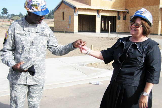 PRESIDIO OF MONTEREY, Calif. - Command Sergeant Major Terry L. Braddock, IMCOM West Region command sergeant major, hands a coin to Gay Rearick during his visit to Ord Military Community's Doe Park in September 2009. Rearick is the manager for the Presidio's RCI project.