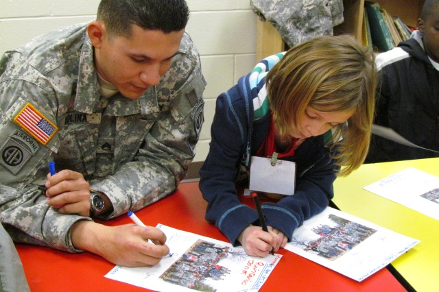 """Staff Sgt. Rob Molina and his charge, survivor Hannah Reid, take turns signing photo pages during the Good Grief Camp for children and teens brought to Bicentennial Chapel by the Tragedy Assistance Program for Survivors Seminar. The photo shows all the children and Soldier mentors attending the TAPS event; and the words """"We Are Not Alone"""" are inscribed at the top of the photo page."""